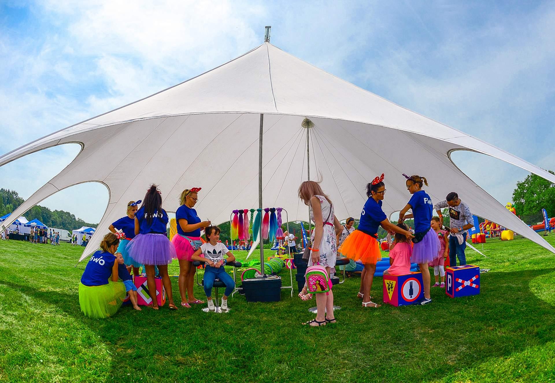 namiot animacyjny, w którym animatorzy plotą kolorowe warkoczyki, malują buźki oraz bawią się z najmłodszymi uczestnikami eventu